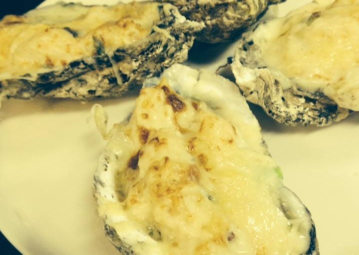 Baked Oyster Rockefeller on a white plate