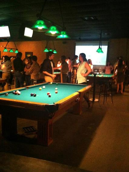 People standing around a billiard table