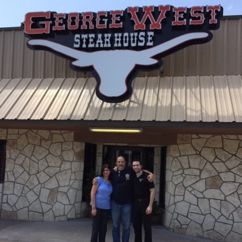 Owners standing in front of George West Steakhouse