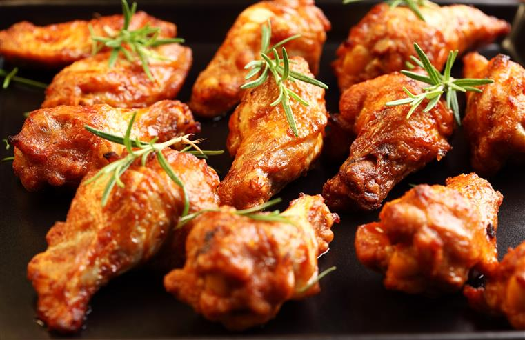 Grilled chicken wings topped with rosemary