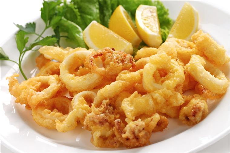 Fried calamari on a white plate with greens and lemon wedges