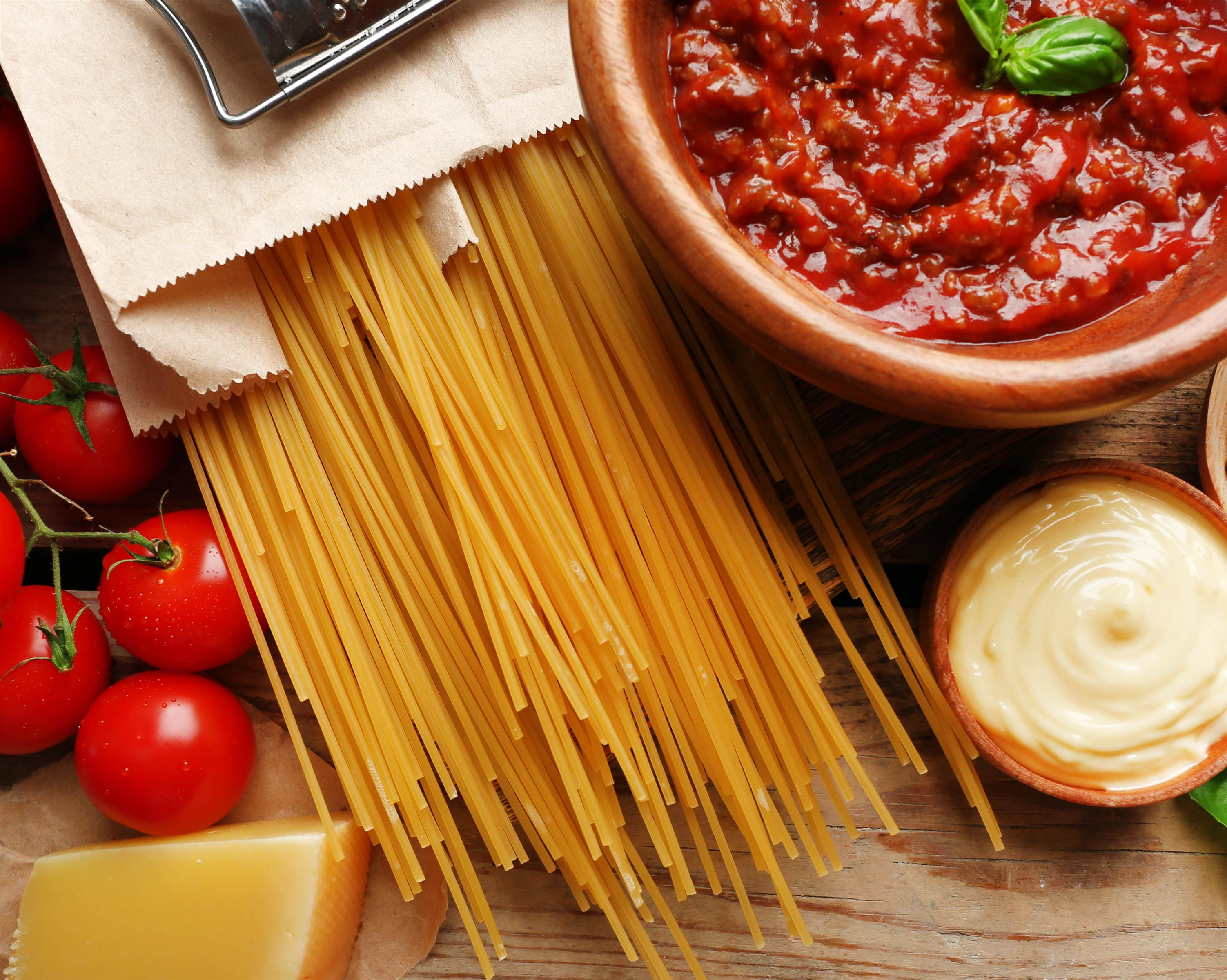 Dry spaghetti in a paper bag on a wooden table with a bowl of tomato sauce next to tomatoes on the vine