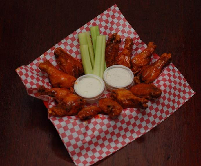 Chicken wings with blue cheese in a basket with carrots, cellery and bleu cheese