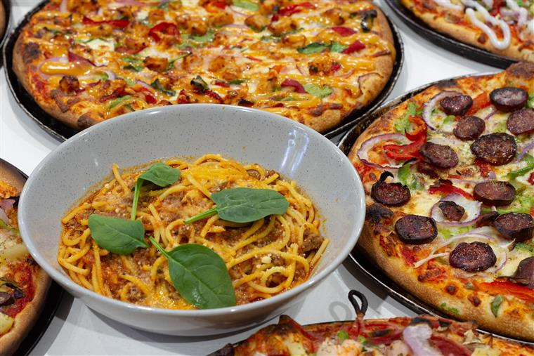 Assorted pizzas on a table with a bowl of spaghetti and meatballs in the center.