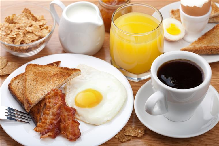 Breakfast with black coffee, orange juice, one sunny side up egg, bacon, two pieces of toast, some milk, and cereal
