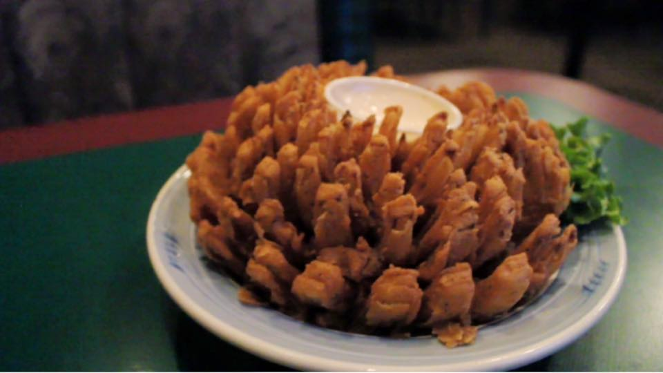 a bloomin onion with dipping sauce