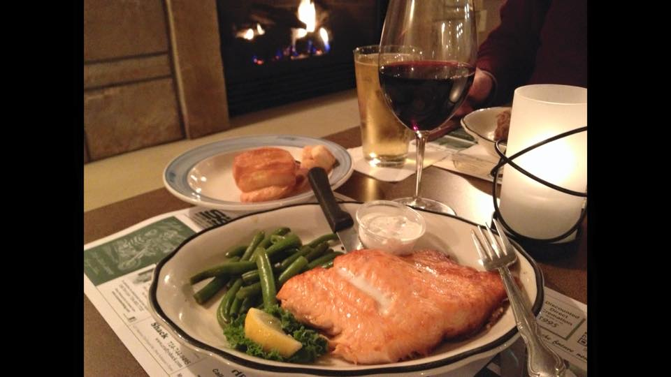 a grilled salmon with a side of string beans, a lemon wedge, and a glass of red wine