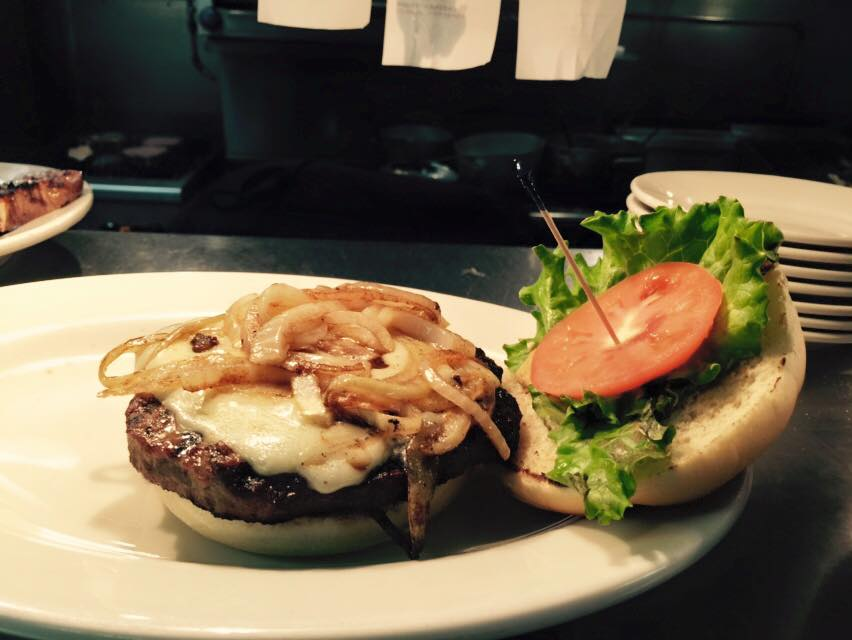 a burger with grilled onions, cheese, tomato and lettuce
