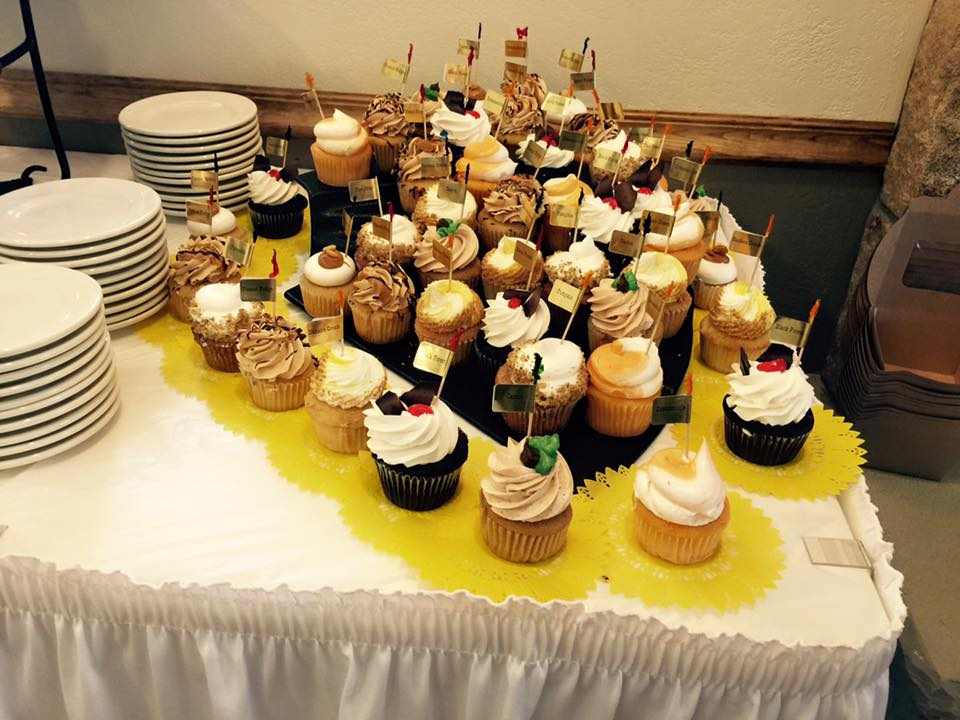 a white table with many different cupcakes on top