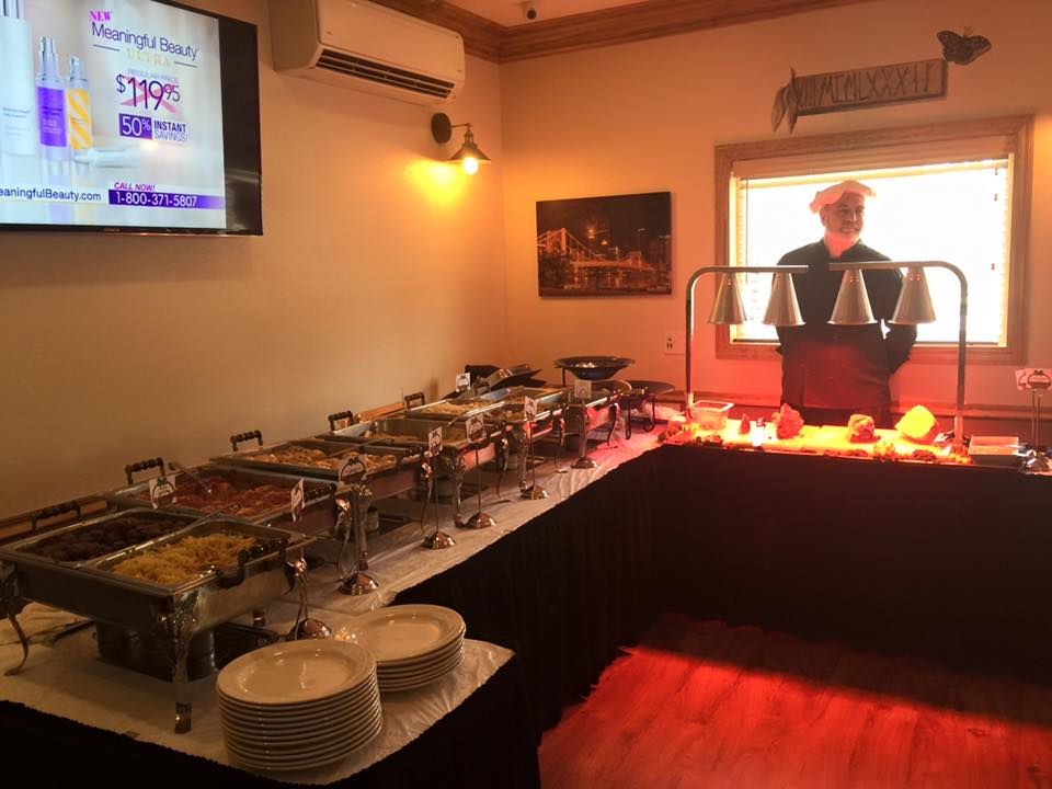 a buffet area showing the hot food and an attendant at the meat area