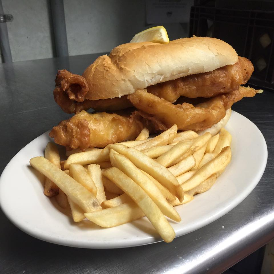 a fried fish sandwich with a side of fries on a  white plate