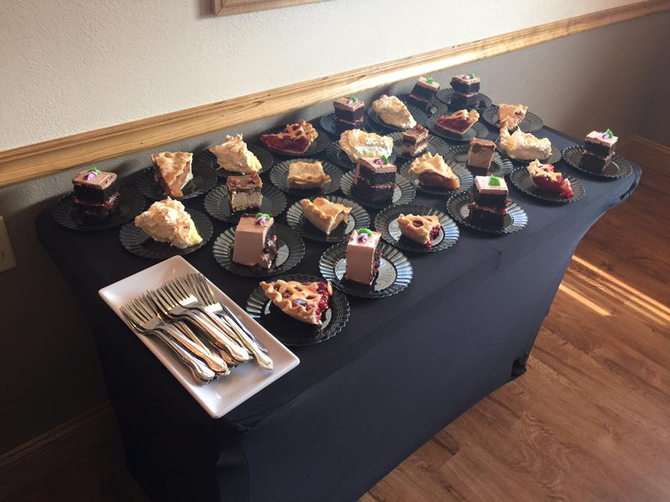 a table with a black table cloth with many different slices of cake