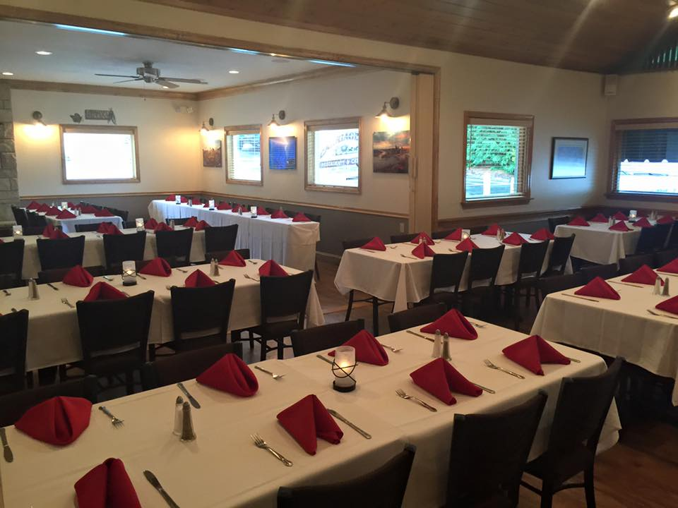 a seating area with long tables with 8 chairs at each table with white table clothes and red napkins