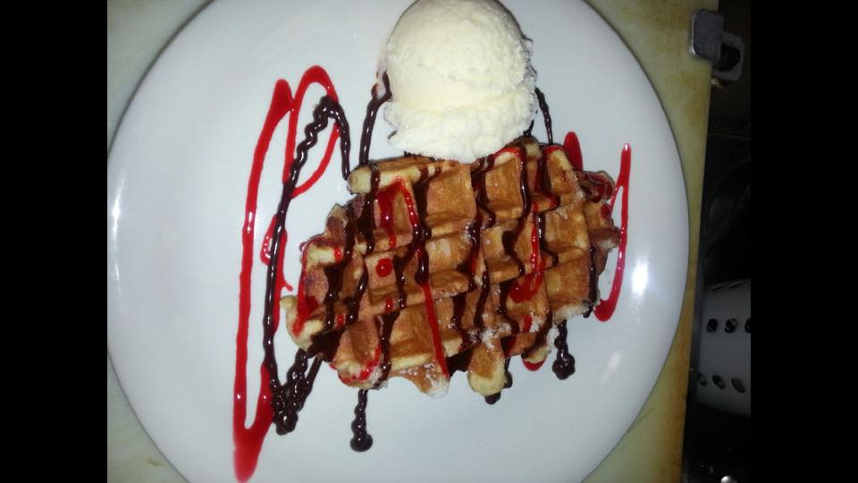 a belgian waffle topped with chocolate and strawberry drizzle and a scoop of vanilla ice cream