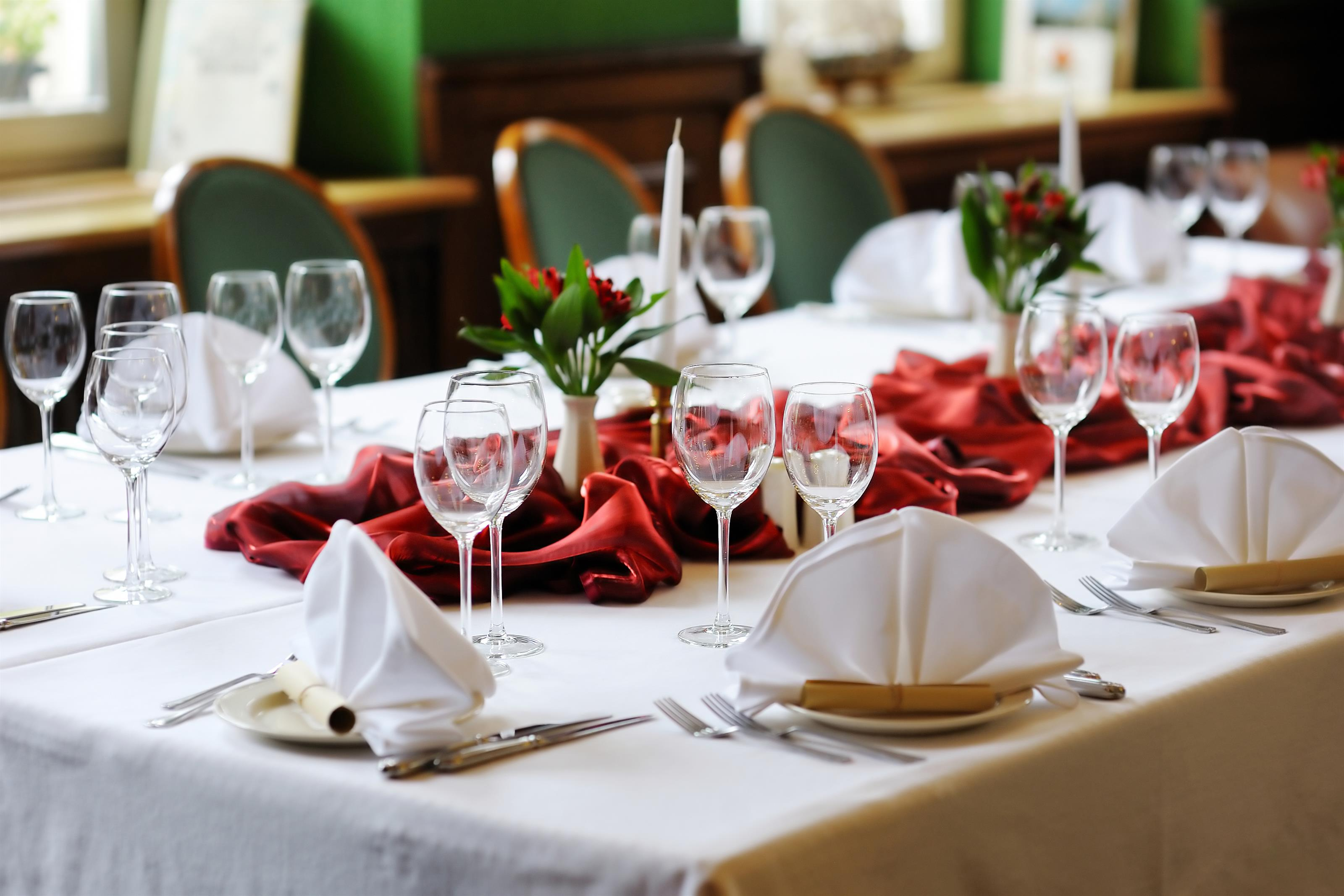 Formal table setting with green and red decorative details