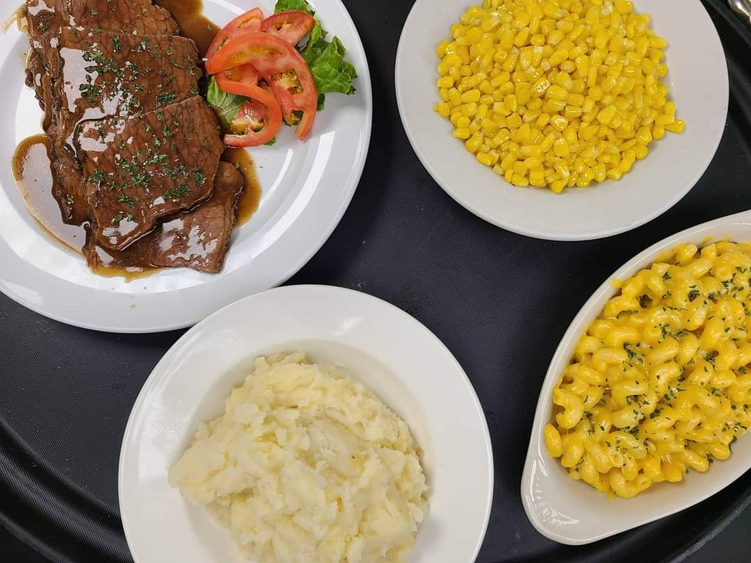 menu items on a tray. meat with gravy, a side of corn, a side of mashed potatoes and mac and cheese