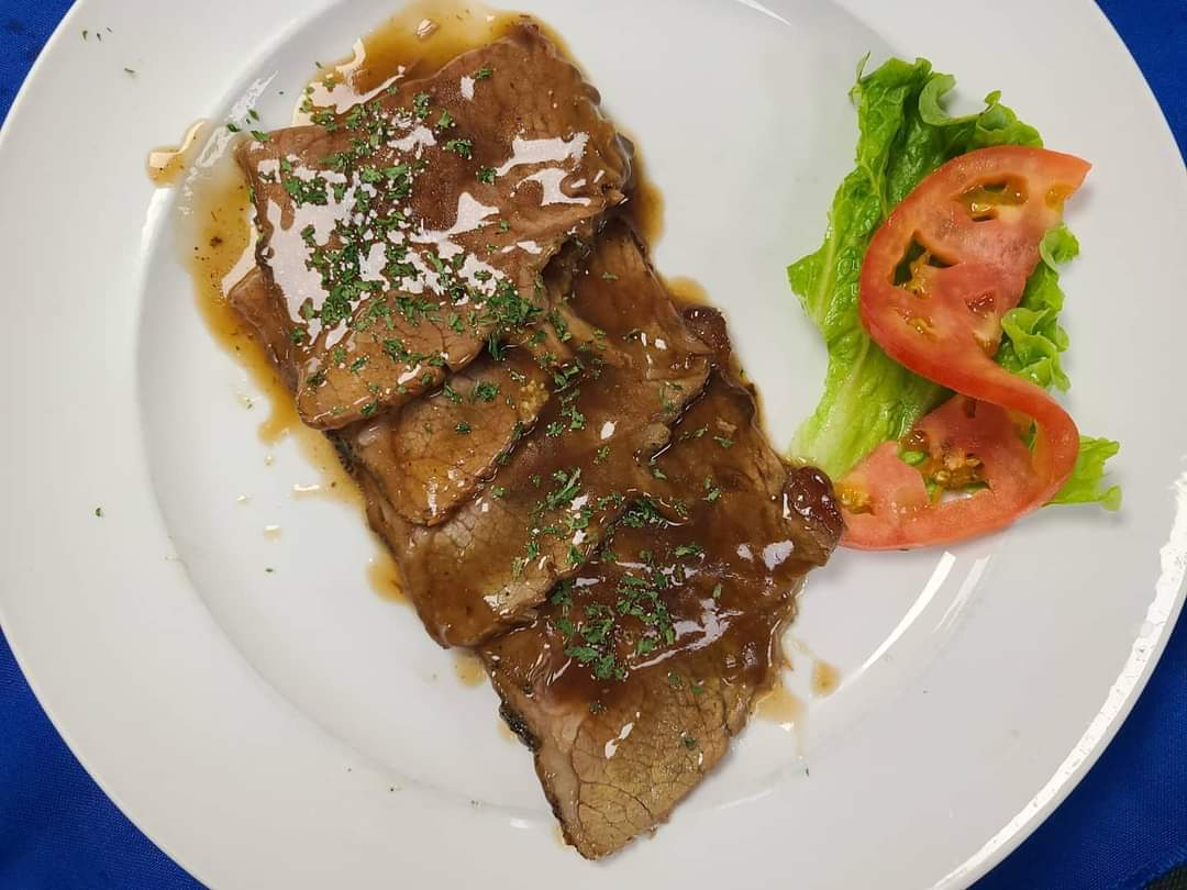 meat menu item with gravy and lettuce and tomato on the side