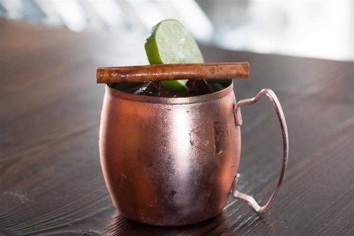 an alcoholic drink in a copper mug sitting on the bar