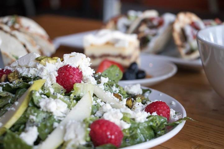 a salad with sliced apples, cheese crumbles, and berries on top