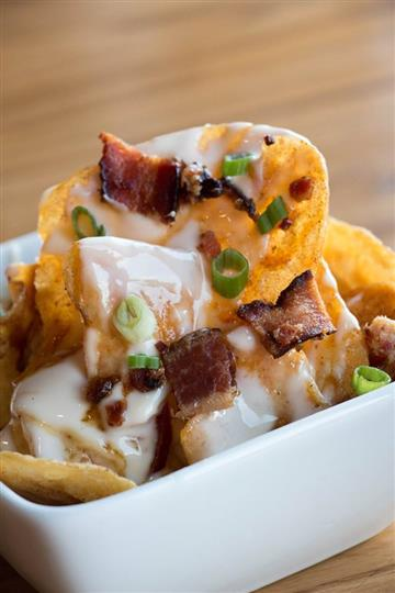 chips with a white sauce, bacon, and scallions on top