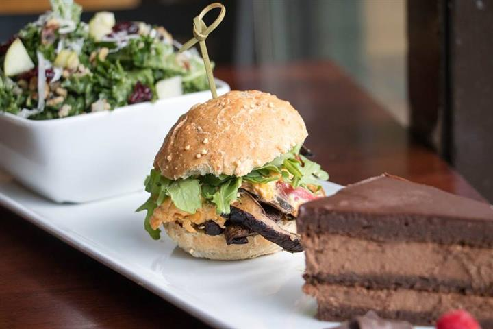 a side salad, a slider, and a piece of chocolate cake on a plate