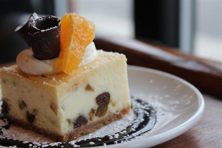 a piece of cheesecake with cream, chocolate, and a peeled orange slice on top