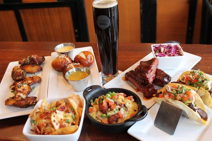 a plate of pretzel bites with 2 dipping sauces, a bowl of nachos, and plate of ribs with a side salad, and a bow of chopped vegetables and meat.