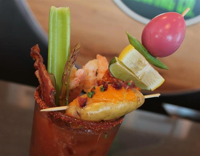 a bloody mary with bacon, celery, lemon, lime, and a tomato on top