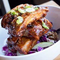 a pile of ribs on top of cabbage in a bowl