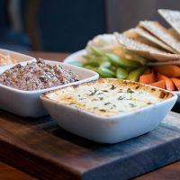 3 different dips and a platter of vegetables and pitas
