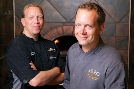 Owners of Peel Wood Fire Pizza Co standing in front of a wood burning oven