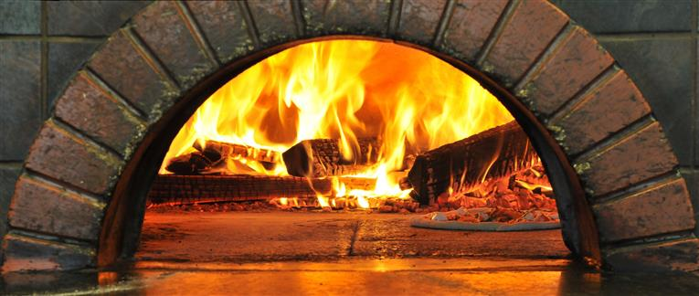 Wood burning oven with pieces of wood on fire with a thin crust pizza being cooked