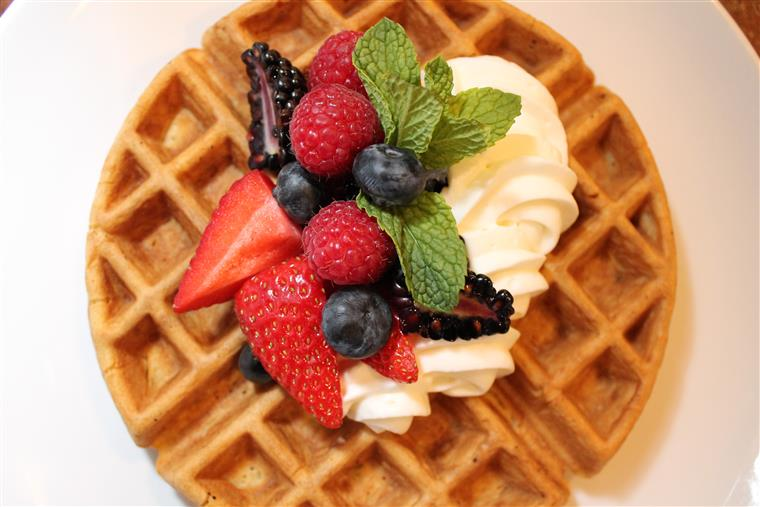 Waffle with whipped cream, fresh fruit, and mint