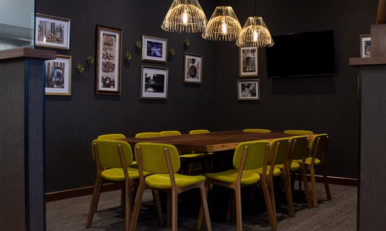 Corporate private room with bright green chairs around a wooden table with pictures on the wall in the background