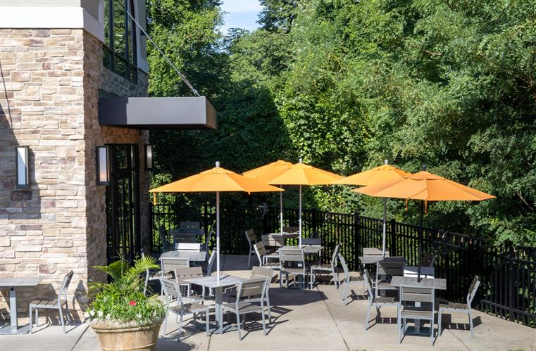 View of tables and chairs with umbrellas one the patio outside of Peel Pizza's Edwardsville location