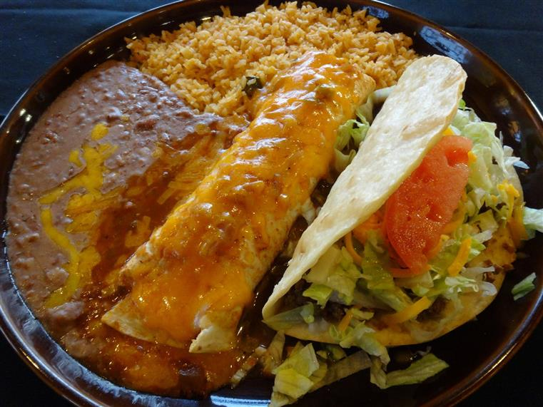 Enchilada and beef taco on a plate with rice and beans