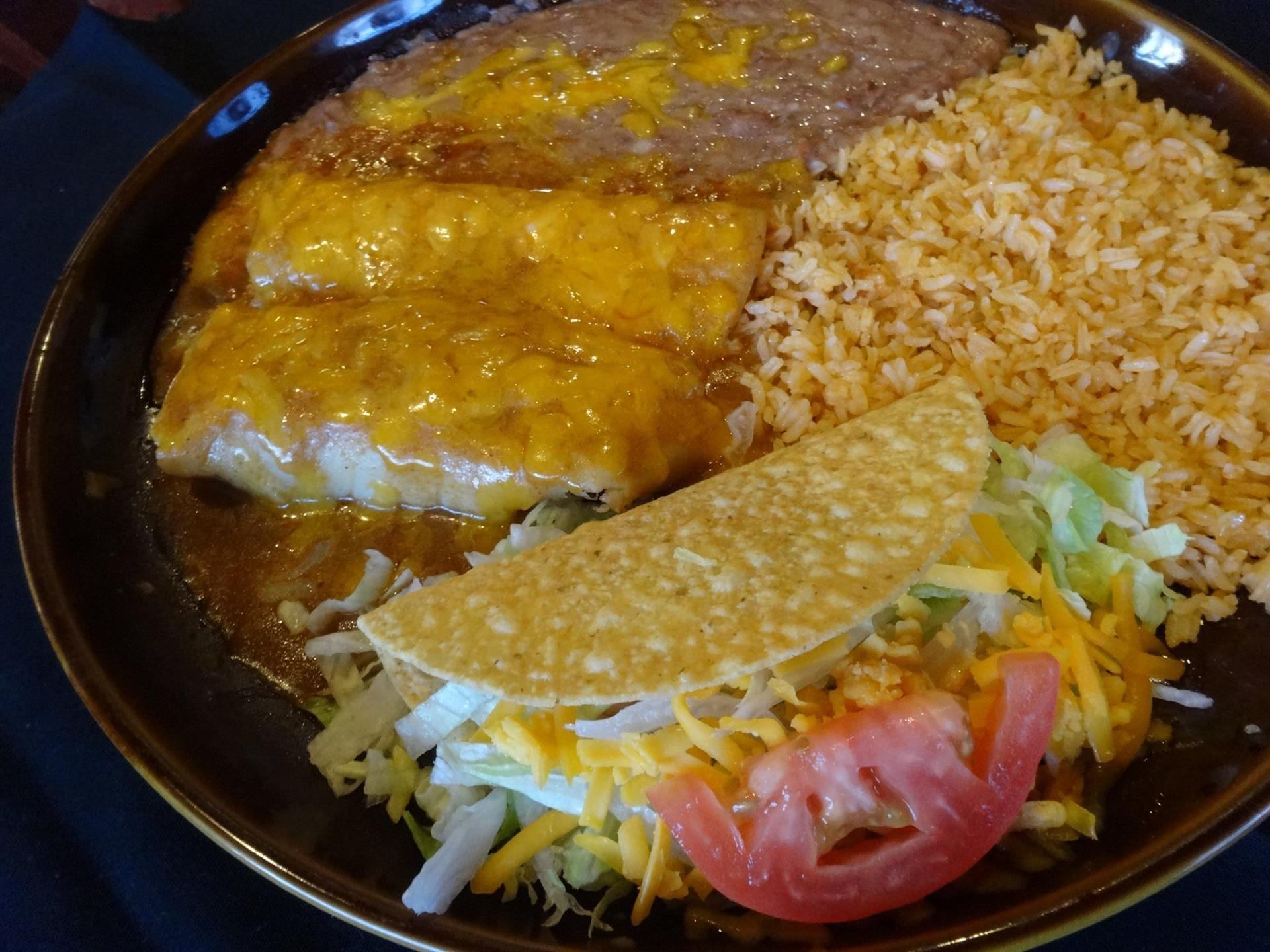 2 enchiladas and a beef taco on a plate with