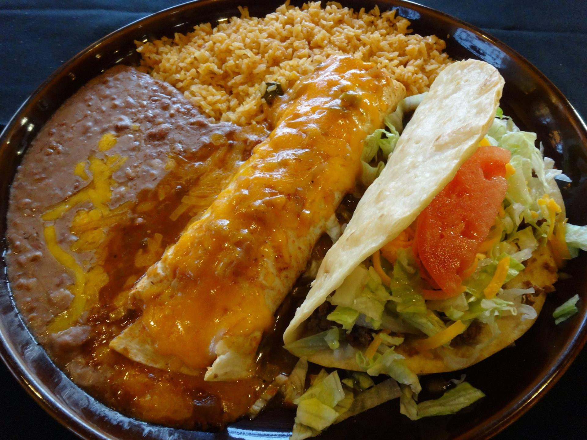 Enchilada covered with cheese. Taco with lettuce and tomato