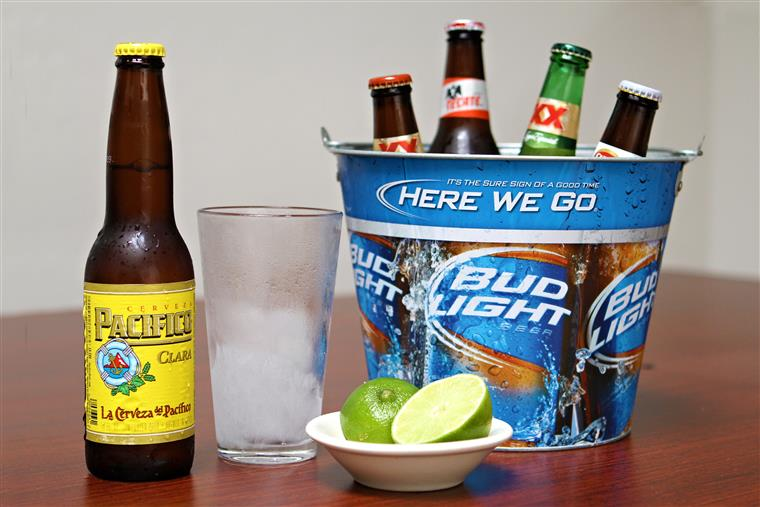 Bud Light bucket filled with assorted bottled beers.  Bottle of Cerveza Pacifico Clara and a chilled pint glass. Limes on the side.