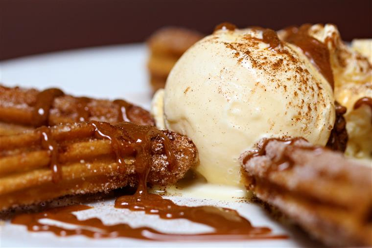 Churros topped with vanilla ice cream and chocolate syrup.