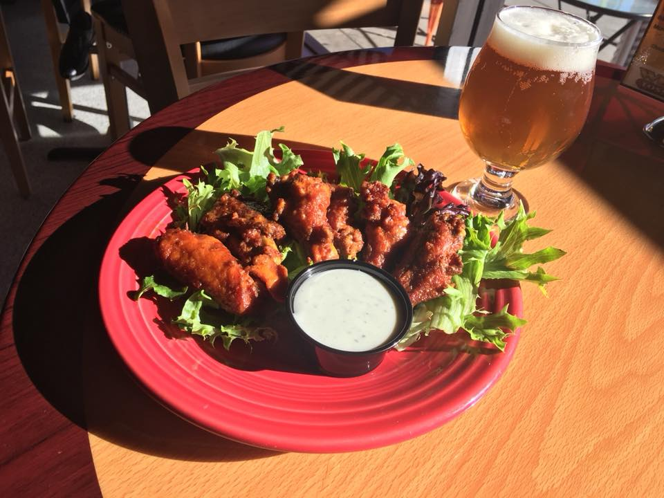 Chicken wings on a plate with bleu cheese and a pint of beer