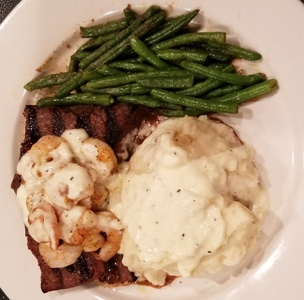 1/2 pound Pub Sirloin topped with grilled shrimp. Mashed potatoes and green beans on the side.