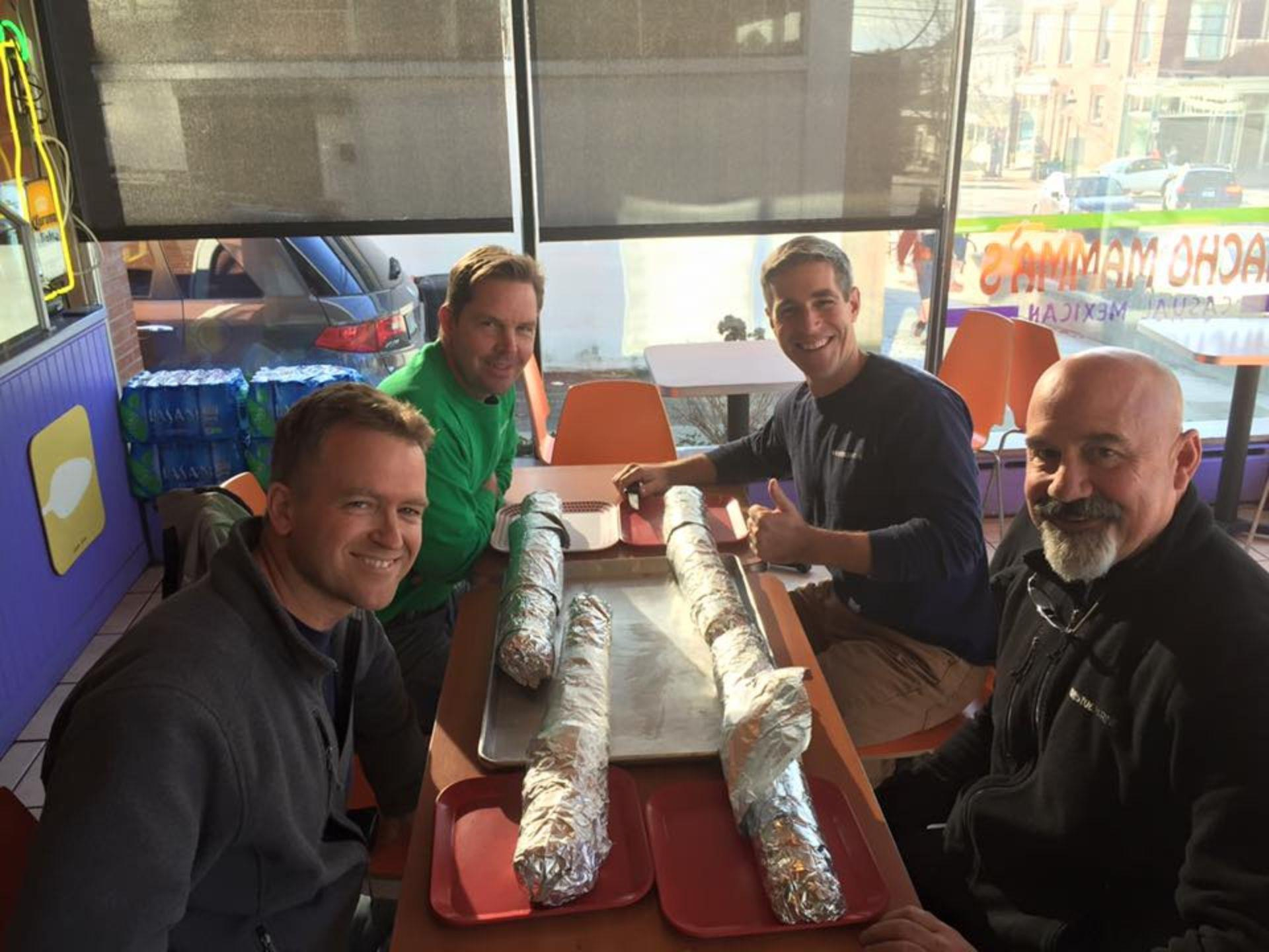 4 customers sitting at a table ready for the burrito challenge