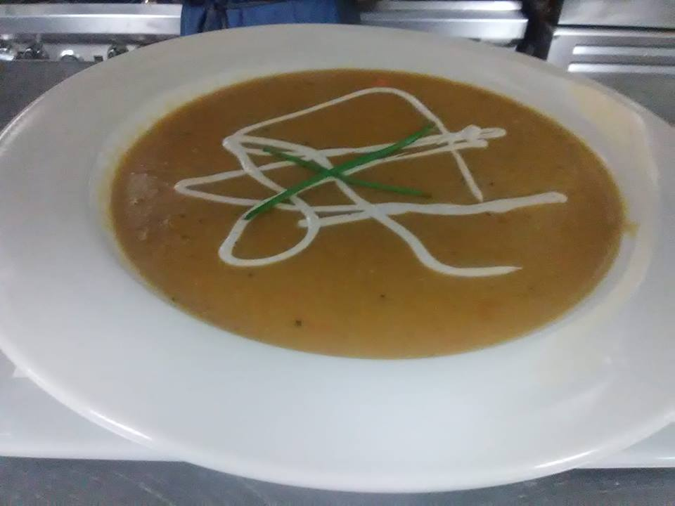 soup in a white bowl with a cream drizzle