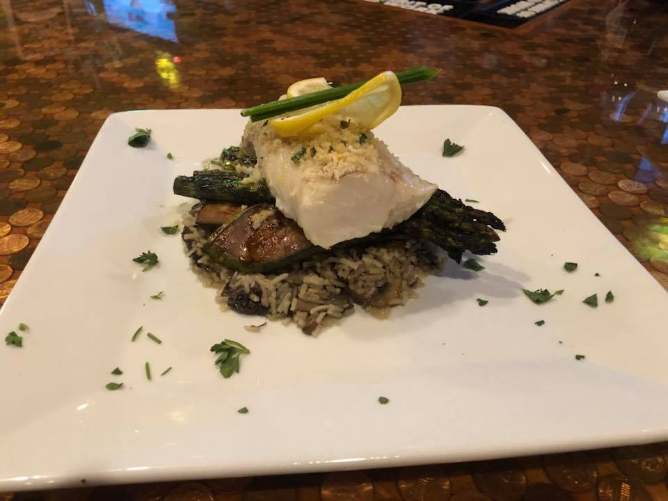 fish served over asparagus and rice on a large white plate