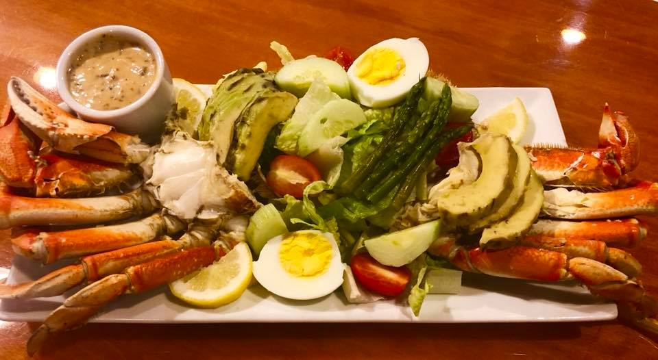 crab legs with hard boiled eggs, acovados and asparagus  with a brown sauce and lemon slices