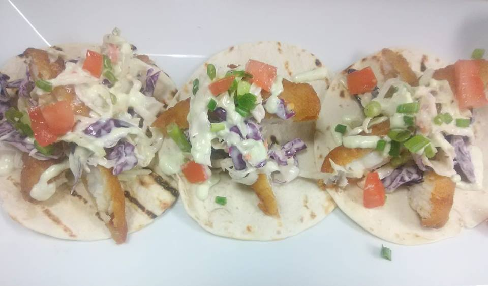 three fish tacos  with slaw and tomatoes on a white plate
