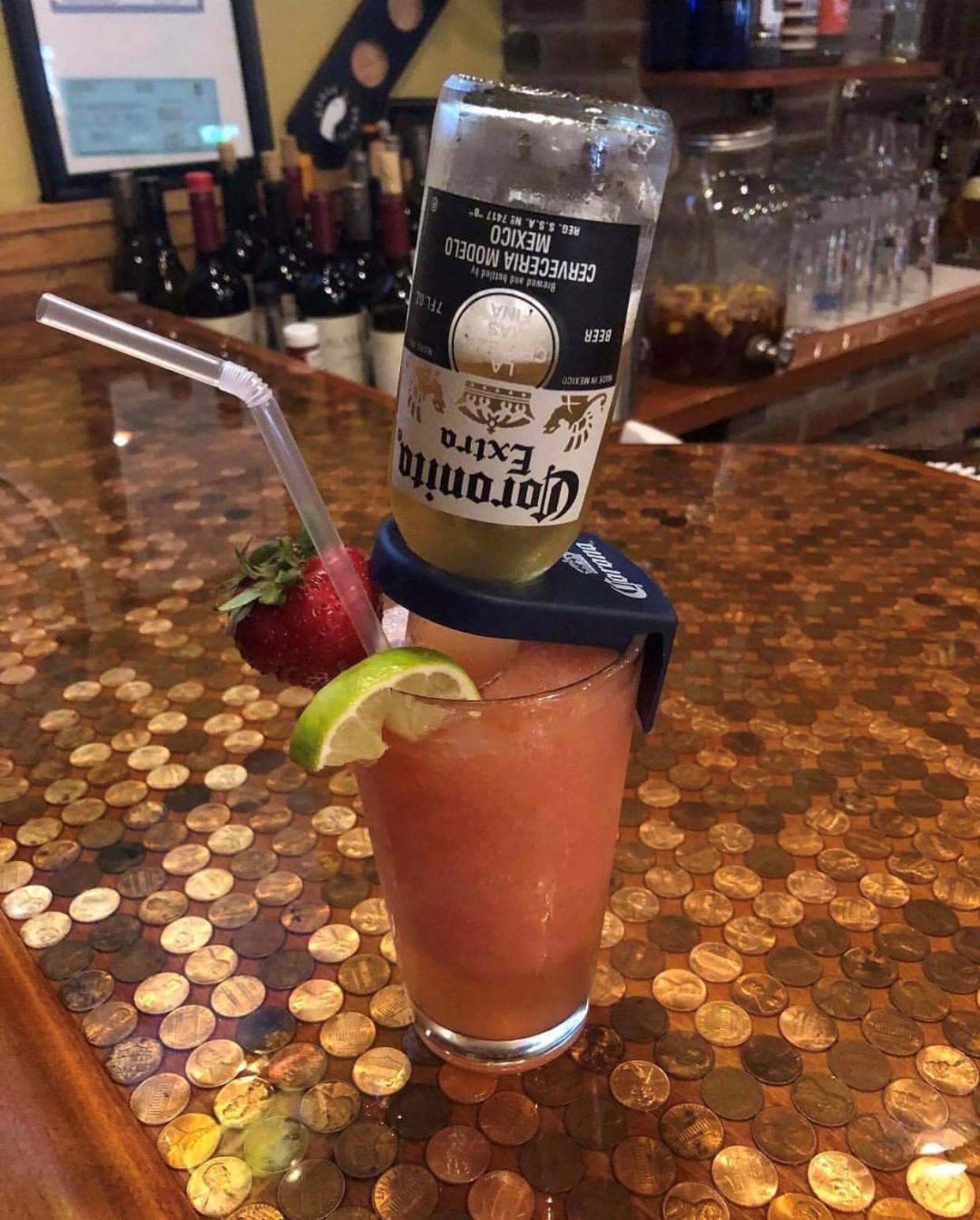 strawberry margarita with a small corona upside down in it