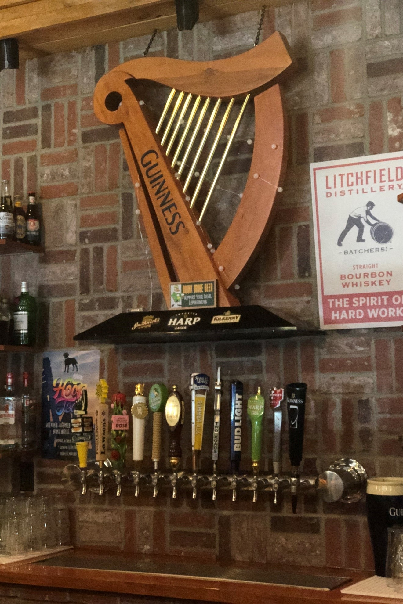 Guinness branded harp on a wall above assorted beer taps behind the bar