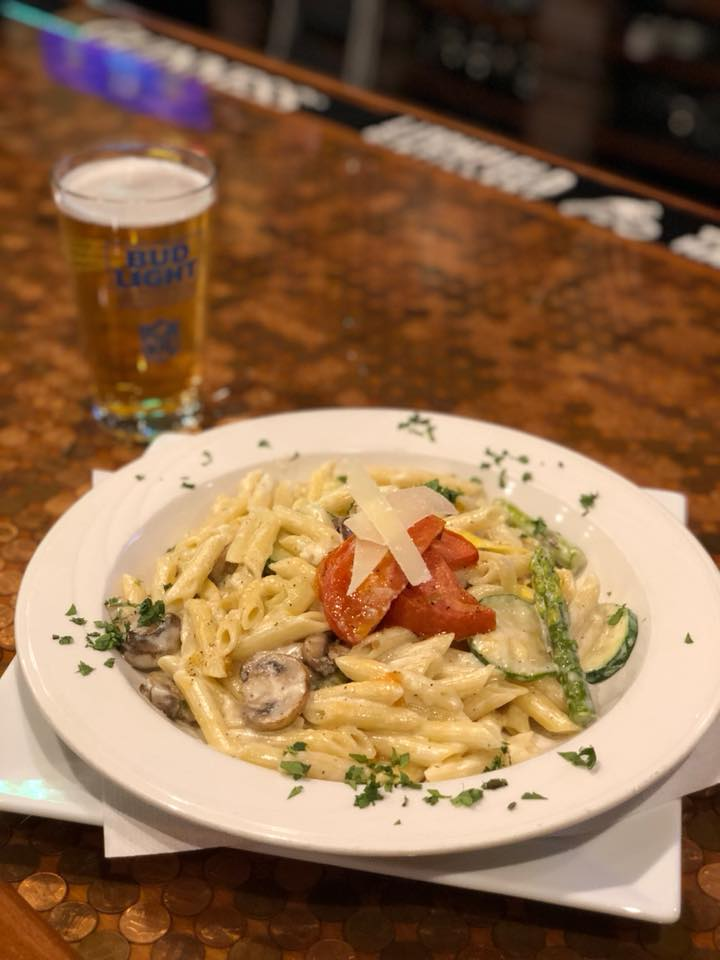 penne pasta in a light cream sauce topped with mushrooms and tomatoes